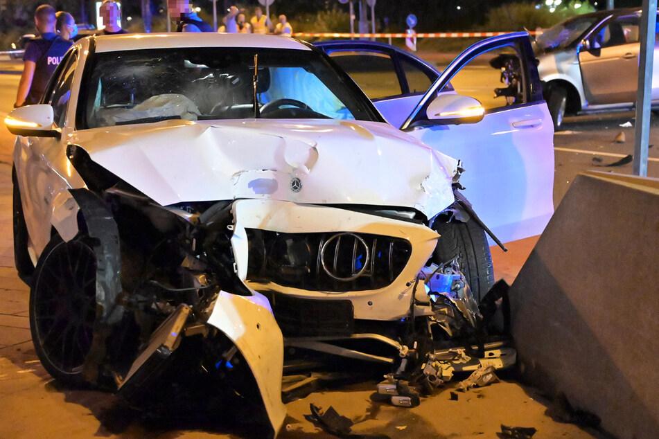 Das Foto zeigt den schwer beschädigten weißen Mercedes und im Hintergrund den ebenfalls beschädigten silberfarbenen Smart.