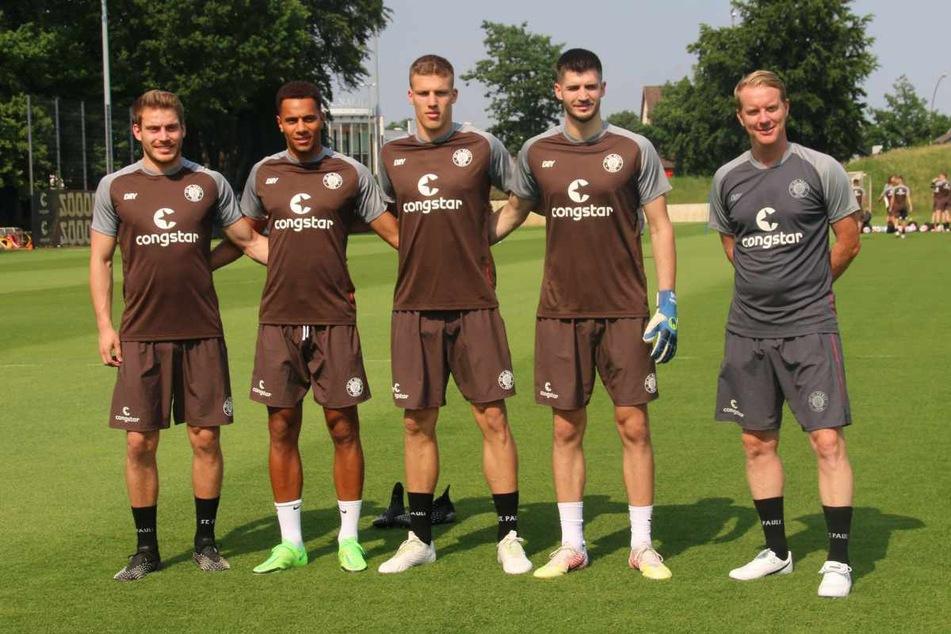 Etienne Amenyido (23, Zweiter von links) posiert vor dem Trainingsstart mit den weiteren Neuzugängen des FC St. Pauli, Lars Ritzka (23v.l.n.r.), Jakov Medic (22) und Nikola Vasilj (25) sowie Trainer Timo Schultz (43).