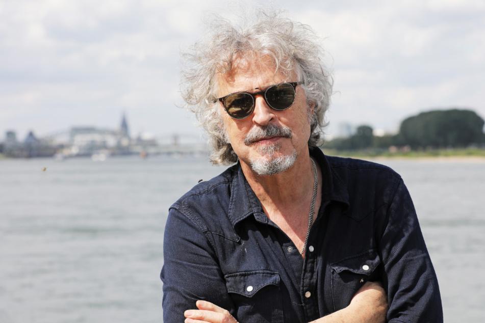 Der Musiker und Sänger Wolfgang Niedecken steht am Rhein.