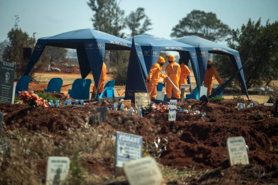 Südafrika, Johannesburg: Arbeiter bereiten eine Beerdigung auf dem Olifantsveil-Friedhof außerhalb der Stadt vor. In Südafrika, als einem der fünf am schwersten von der Corona-Pandemie betroffenen Länder weltweit, hat die Häufigkeit von Bestattungen während der Pandemie stark zugenommen.