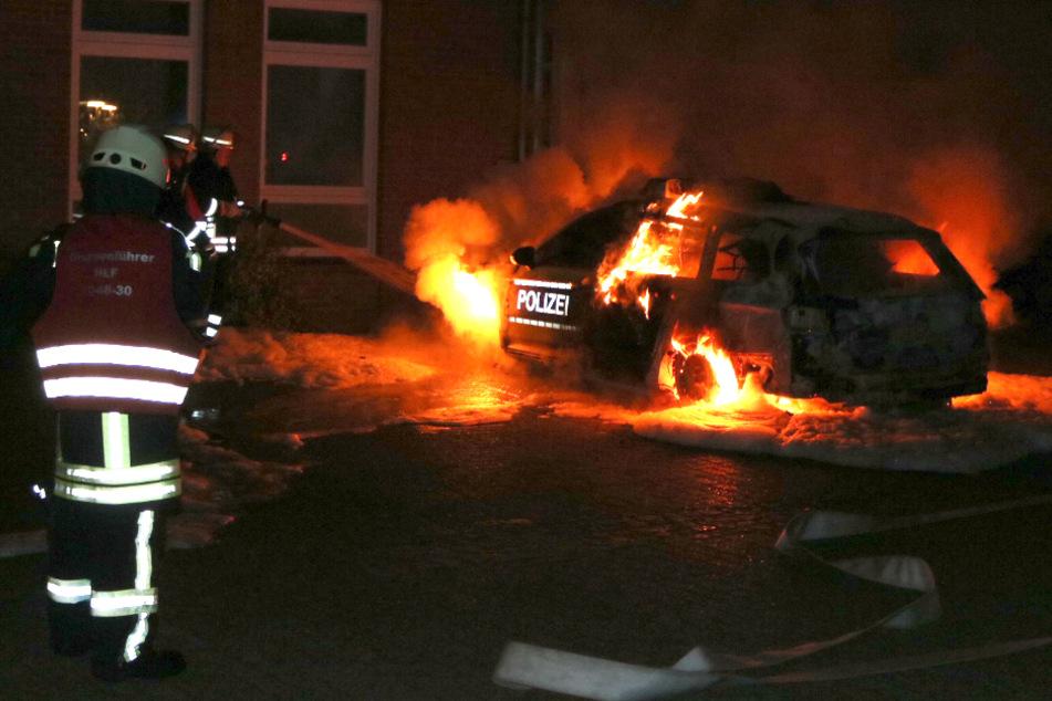 Feuerwehrleute löschen das Polizeiauto in Neuhaus.
