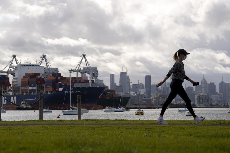 Eine Frau macht einen Spaziergang in der Stadt Melbourne. Wegen der Corona-Pandemie dürfen Ausländer weiterhin nicht nach Australien reisen.