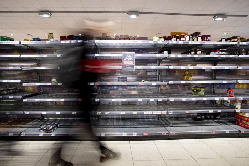 Eine Person geht in einem Supermarkt in Berlin-Wilmersdorf an einem fast leeren Regal vorbei.