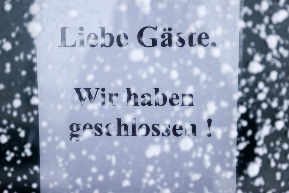 """Ein Schild """"Liebe Gäste, wir haben geschlossen!"""" hängt in einem verschneiten Kasten an einem Restaurant auf dem Fichtelberg."""