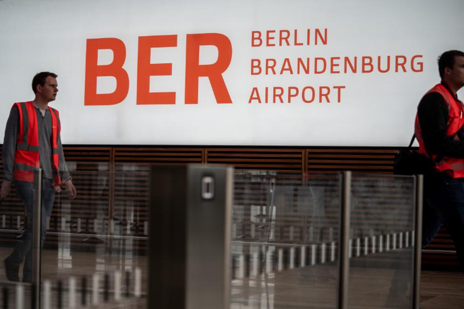 Techniker und Arbeiter sind in der Abflughalle des neuen Flughafens Berlin-Brandenburg Willy-Brandt unterwegs.
