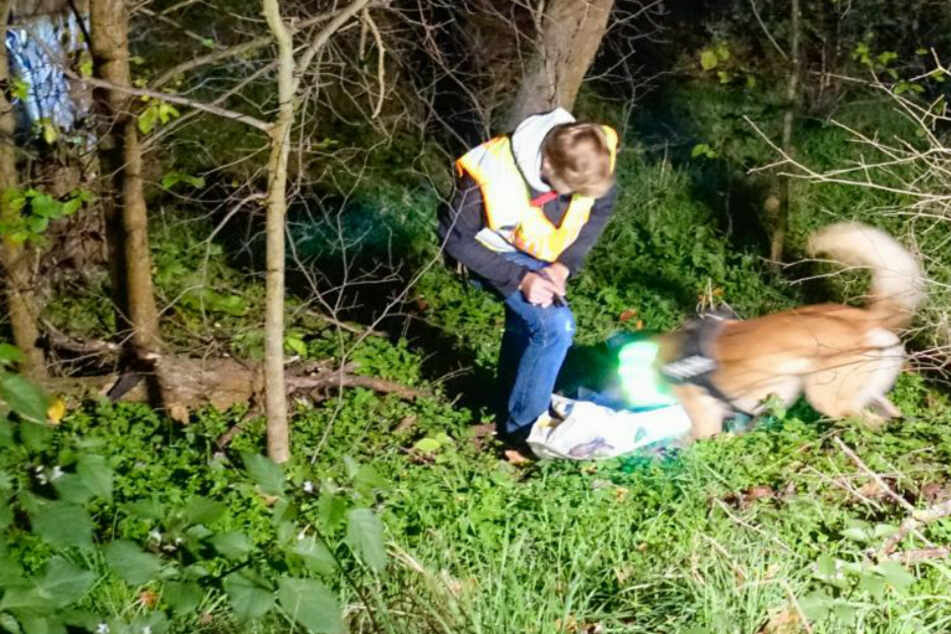 Ein Polizist mit einem Spürhund sucht nach einem vermissten Mann.
