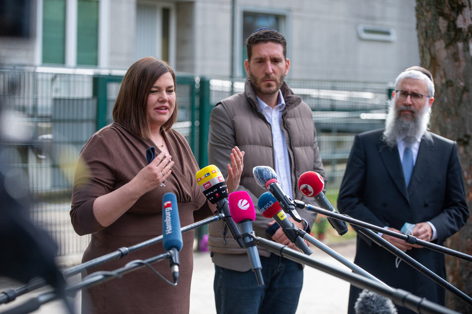 Katharina Fegebank, zweite Bürgermeisterin von Hamburg, gibt ein Statement ab während Philipp Stricharz, erster Vorsitzender der Jüdischen Gemeinde Hamburg, und Shlomo Bistritzky, Landesrabbiner von Hamburg neben ihr stehen.