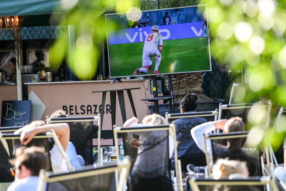 Zahlreiche Menschen sitzen auf Liegestühlen am Sonntagabend im James-Simon-Park und schauen sich ein Spiel der Fußball-EM an.
