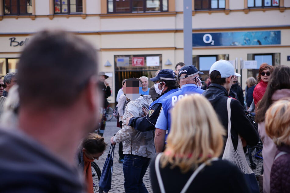 Beamte der Polizei während sie den Mann beiseite nehmen, der zuvor versucht hatte, eine Rede zu halten und nach einer Absage durch die Organisatoren aggressiv geworden war.