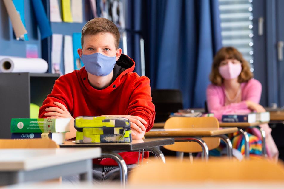 Schüler und Schülerinnen einer 12. Klasse nehmen am Unterricht teil und tragen Mundschutze. (Symbolbild)