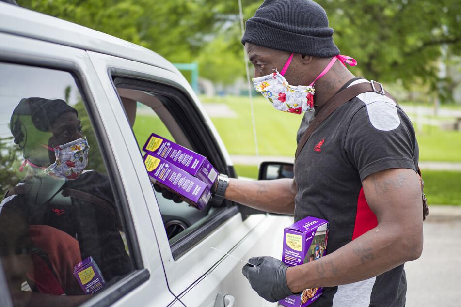 """USA, Des Moines: Nadir Shibaz (r), ein Freiwilliger bei der """"Emergency Food Distribution"""" , übergibt mehrere Packungen Kekse an Bedürftige in einem Auto. Allein in Iowa haben sich seit Beginn der Corona-Pandemie fast 190.000 Menschen als arbeitslos gemeldet."""