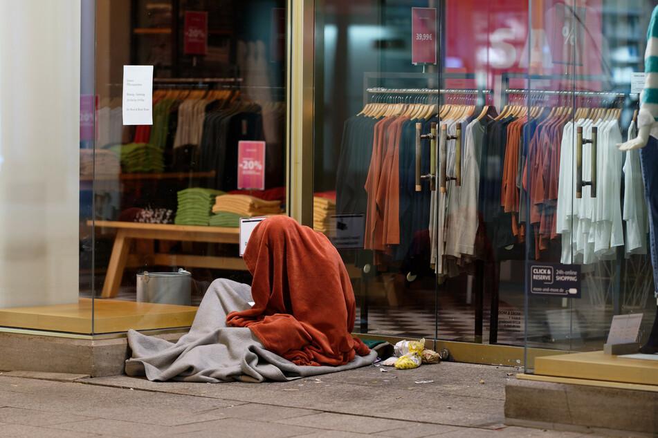 Ein Obdachloser in der Kölner Innenstadt ist bei Eiseskälte in dünne Decken gehüllt.