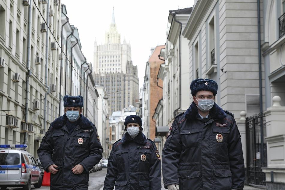 Russische Polizeibeamte mit Mundschutz patrouillieren in einer fast leeren Straße.