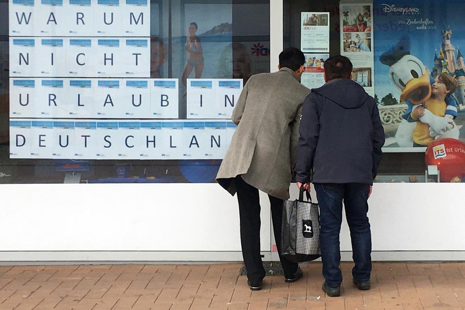 """""""Warum nicht Urlaub in Deutschland"""": Zwei Männer schauen in Dortmund in das Schaufenster eines Reisebüros."""