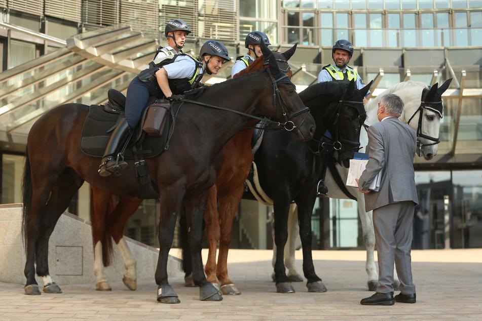 Der nordrhein-westfälische Innenminister Herbert Reul (68, CDU, r.) spricht am Landtag mit Polizeibeamten der Reiterstaffel.