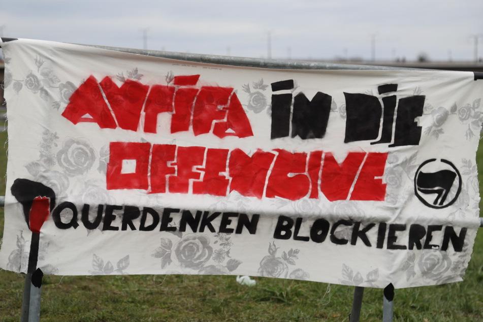 """Gegenprotestler haben ein Banner gespannt: """"Antifa in die Offensive - Querdenken blockieren"""", steht darauf."""