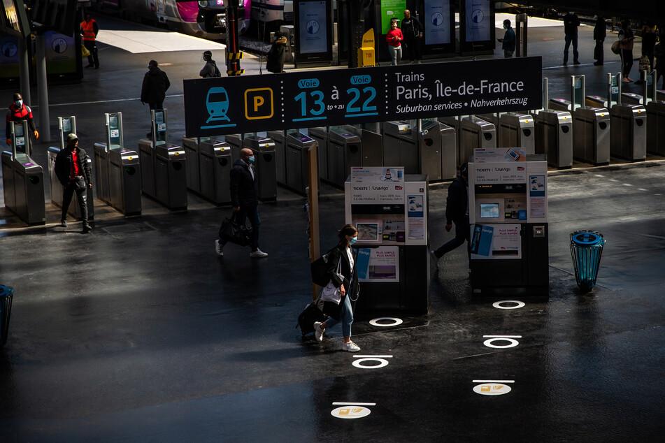 """Paris: Fahrgäste gehen in der Halle des Pariser Bahnhofs """"Gare du Nord"""", wo Bodenmarkierungen sie auf den Abstandsbegrenzung hinweisen."""