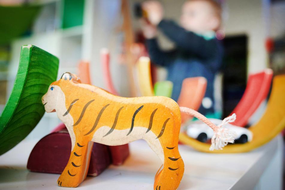 Ein Junge spielt in einer Kindertagesstätte hinter einer Tigerfigur mit Bauklötzen und einem Spielzeugauto.