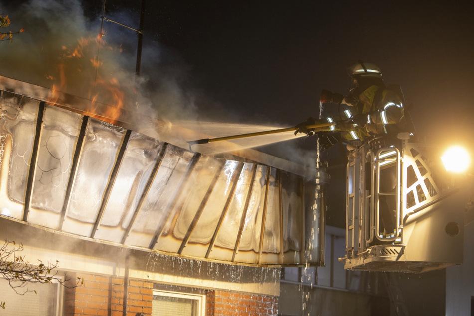 Feuerwehrleute löschen von einer Drehleiter aus den Dachbrand.