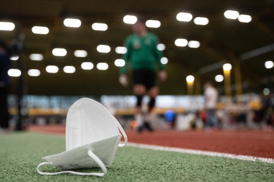 Eine FFP2-Maske liegt auf dem Boden neben der Laufbahn.