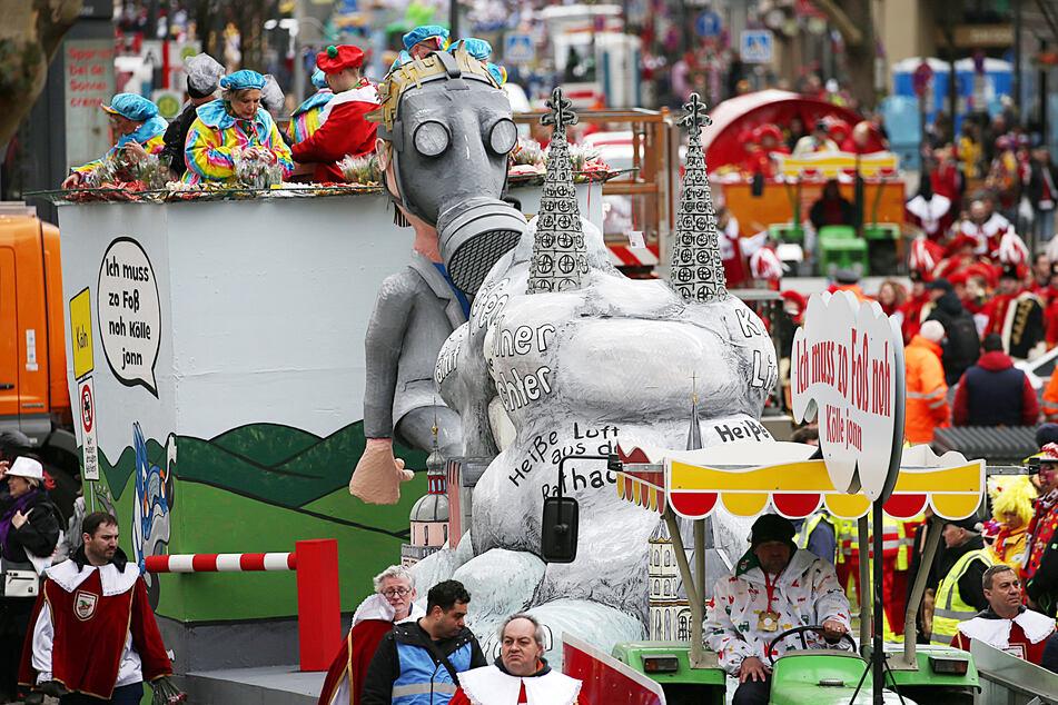 Ein Mottowagen zum Thema Luftverschmutzung in den Städten fährt im Rosenmontagsumzug in Köln mit.