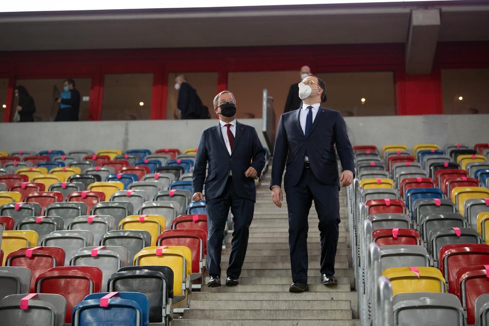 """Jens Spahn (CDU, r), Bundesgesundheitsminister, und Armin Laschet (CDU), Ministerpräsident von Nordrhein-Westfalen, gehen durch den Innenraum des Düsseldorfer Fußballstadion """"Merkur Spiel-Arena""""."""