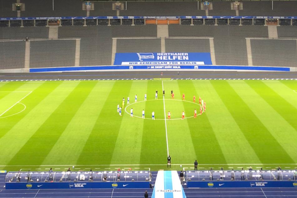 Die Spieler von Hertha BSC und Union Berlin stehen auf dem Spielfeld im leeren Stadion.