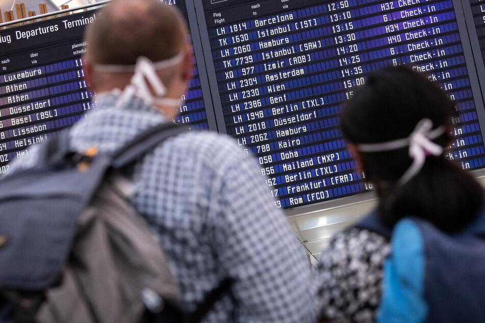Reisende mit Mundschutz schauen auf eine Anzeigetafel am Münchner Flughafen, auf der zahlreiche internationale Flugziele gelistet sind. (Archivbild)