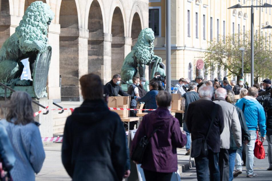 Mitarbeiter der Stadt Dresden verteilen vor dem Rathaus Mundschutzmasken.