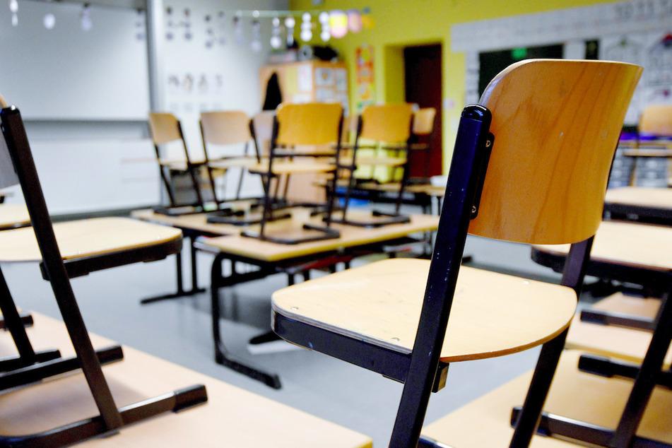 Stühle stehen in einem Klassenzimmer in einer Grundschule auf den Tischen.