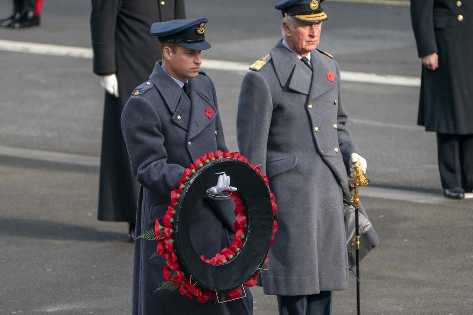 Prinz William (l), Herzog von Cambridge, hält bei der Gedenkfeier neben Prinz Charles, Prinz von Wales, einen Mohnblumenkranz in der Hand.