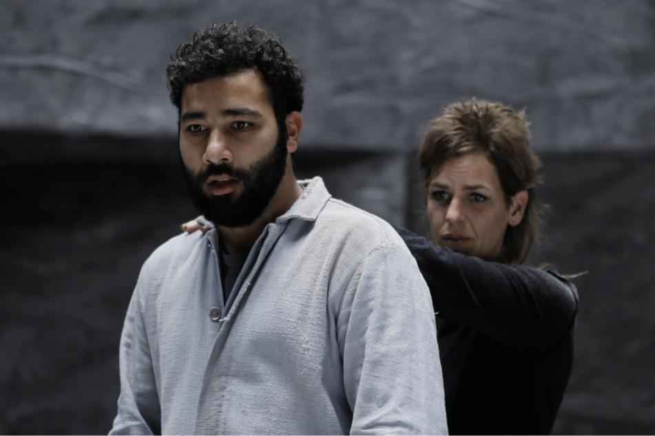 Alihan Jabir (l., Ibrahim Al-Khalil) fürchtet sich vor den Hunden, die ihn und die anderen angreifen. Lu (Nadin Matthews) will ihm helfen, seine Angst zu überwinden.