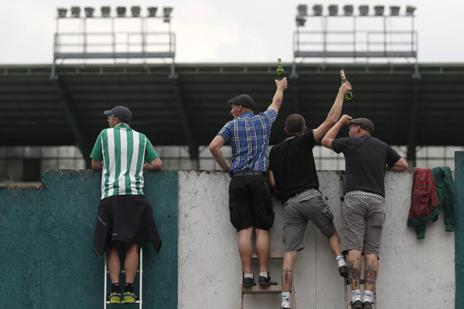 Fans sind mit einer Leiter auf eine Mauer geklettert, um ihre Teams anzufeuern. Aufgrund der begrenzten Zuschauerzahl dürfen nur wenige Dutzend Fans das Erstligaspiel zwischen Bohemians Prag 1905 und FK Jablonec von der Tribüne aus verfolgen.