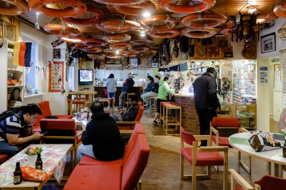 """Besucher des Seemannsclubs """"Duckdalben"""" sitzen im Multifunktionsraum mit Bar, Kantine und Einkaufsladen."""