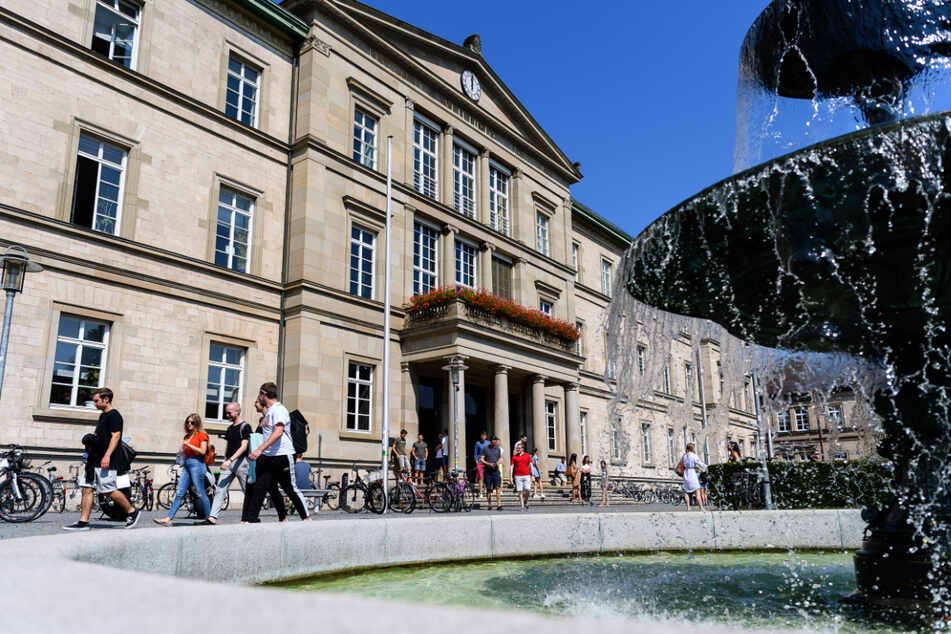 Studentinnen und Studenten laufen vor der Neuen Aula der Universität Tübingen an einem Brunnen vorbei. (Archivbild)