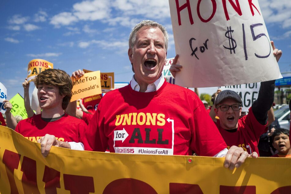 Already in 2019, Bill De Blasio (center) stood with fast food workers, calling on McDonald's to raise its minimum wage to $15 per hour and improve worker safety.