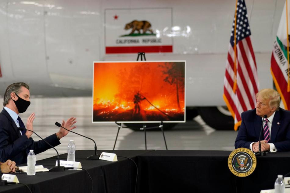 Donald Trump hört zu, als der kalifornische Gouverneur Gavin Newsom während eines Gesprächs auf dem McClellan-Flughafen von Sacramento über die Waldbrände im Westen spricht.