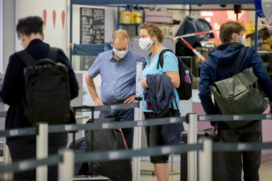 Passagiere stehen mit Mundschutz am Flughafen Berlin-Tegel vor einem Check-in-Schalter an.
