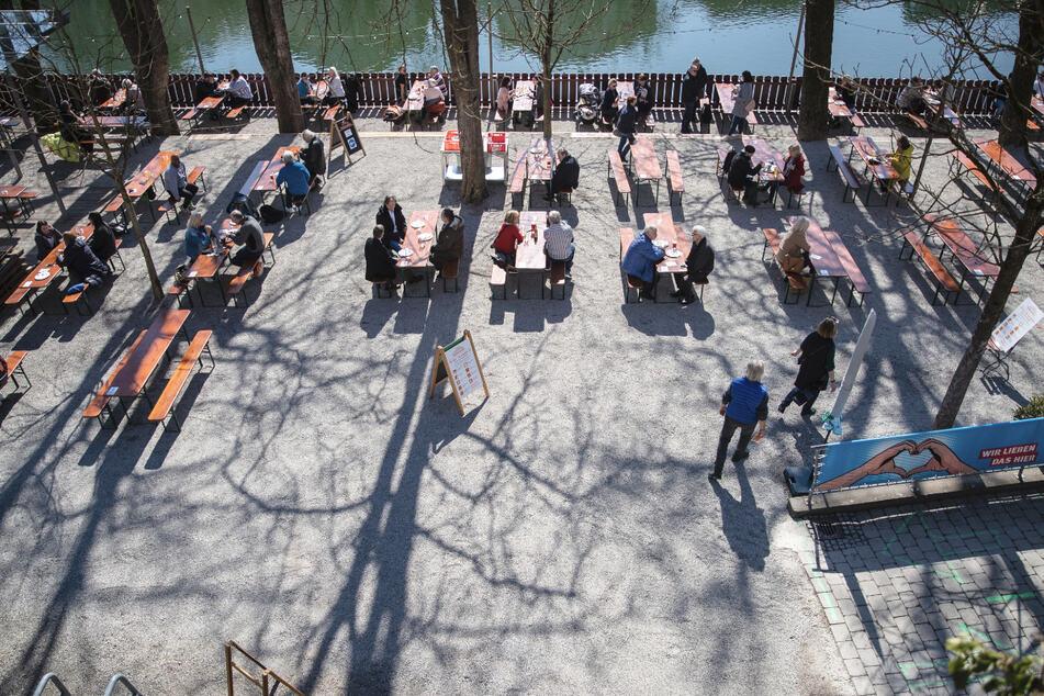 Menschen sitzen bei gutem Wetter in Tübingen in einem Biergarten. Dank des Tagestickets sind Besuche in der Außengastronomie möglich.