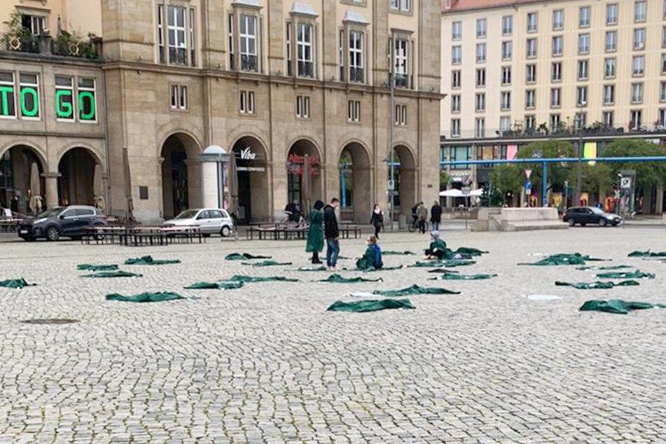 """Auf dem Altmarkt protestierten einige Pfleger, indem sie zeitweise in grünen Regencapes auf dem Boden lagen. """"Klatschen hilft nicht"""" stand auf ihren Transparenten."""