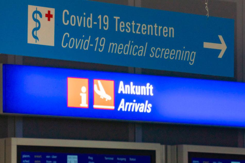 Ein Schild weist am Flughafen im Ankunftsbereich zum Covid-19-Testzentrum.