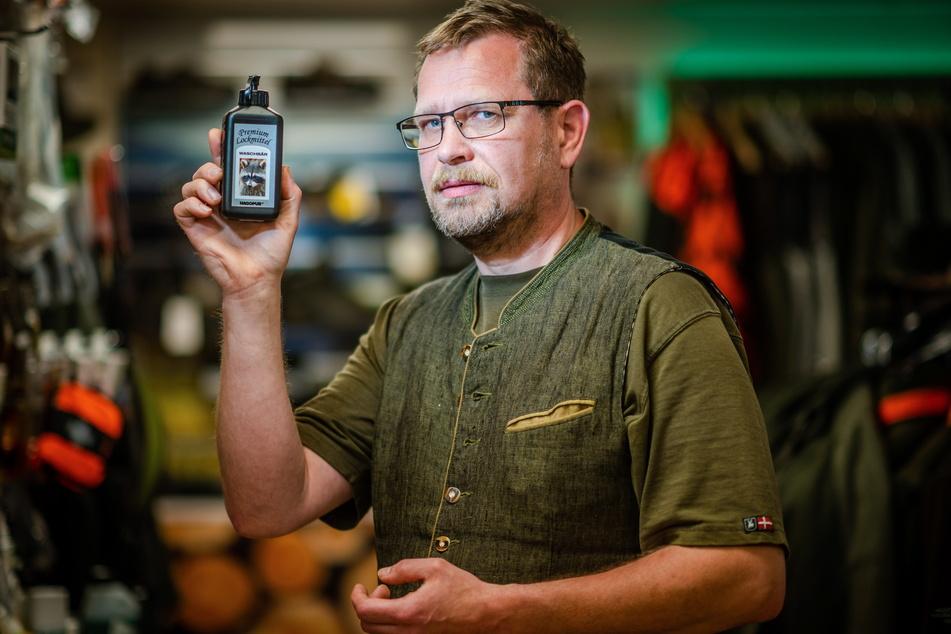 Jäger André Pöschl (52) aus Schwarzenberg hält ein Lockmittel für Waschbären in der Hand.