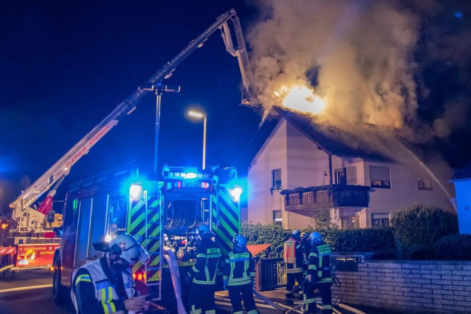 Mit Atemschutz-Geräten ausgestattete Feuerwehr-Leute retteten die schwer verletzte Person aus dem brennenden Haus.
