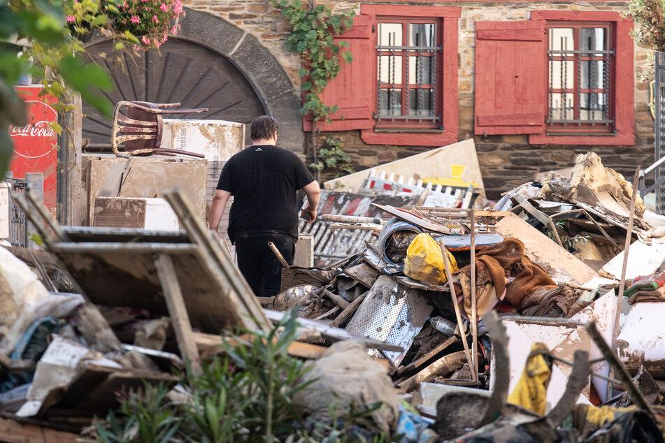 Ein Anwohner läuft in der Innenstadt von Ahrweiler (Rheinland-Pfalz) durch Unrat und aufgetürmte Einrichtungsgegenstände aus den zerstörten Häusern und Wohnungen.