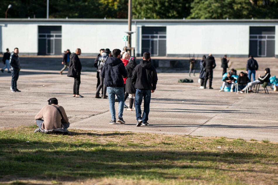 Asylsuchende laufen in der Erstaufnahmeeinrichtung Eisenhüttenstadt über einen Platz. Seit August ist die Zahl der Flüchtlinge, die über die Belarus-Route illegal nach Deutschland einreisen, sprunghaft angestiegen.