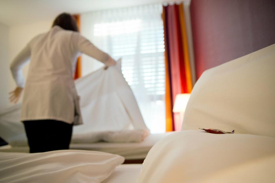Ein Zimmermädchen macht Betten in einem Hotel.