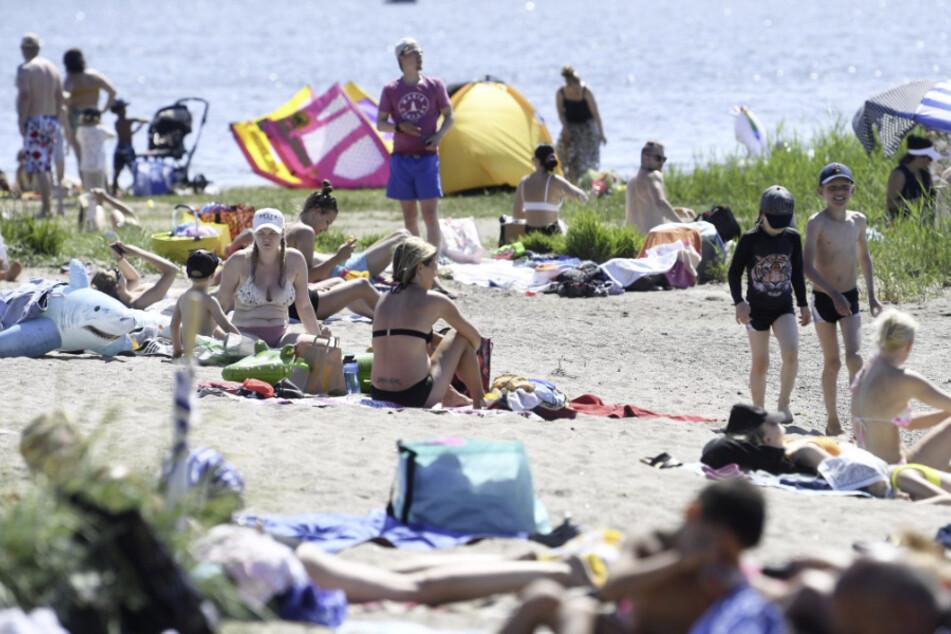 Finnland, Helsinki: Menschen genießen den heißen, sonnigen Tag an einem Strand. (Archivbild)