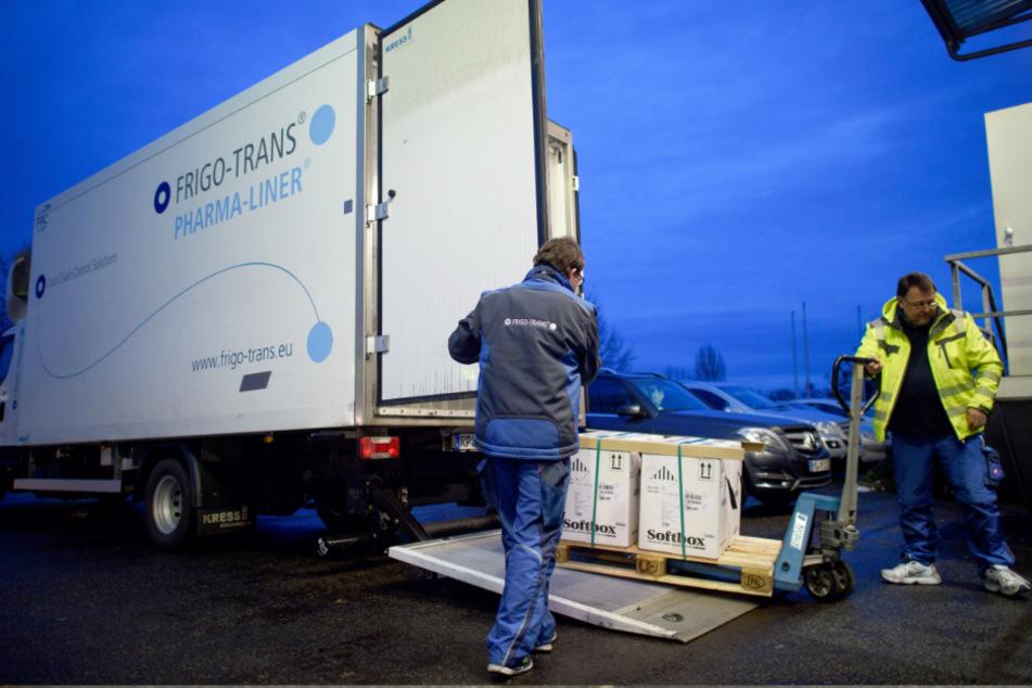 Fahrer eines Kühllastwagens entladen in einem Logistikzentrum Kisten mit Impfdosen von Biontech/Pfizer.