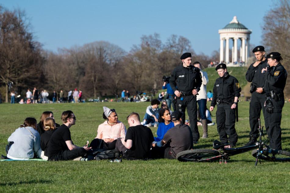 Polizisten reden im Englischen Garten mit einer Gruppe Jugendlicher. (Symbolbild)