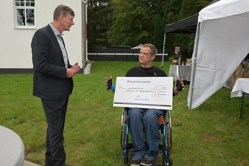 """Uwe Bauch (56, l.), Vorstandsvorsitzender von """"community4you"""", übergibt Sascha Stoltze (48) vom Verein Miteinander statt Gegeneinander einen Spendencheck."""